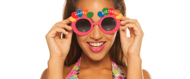 Bautiful girl celebrating wearing birthday sunglasses on white Royalty Free Stock Photos