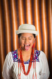 Bautiful hispanic model wearing andean traditional clothing with matching white hat, holding tongue out for camera Royalty Free Stock Images