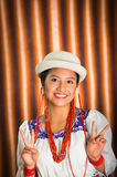 Bautiful hispanic model wearing andean traditional clothing with matching white hat, smiling and interacting making Royalty Free Stock Image