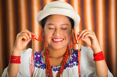Bautiful hispanic model wearing andean traditional clothing with matching white hat, smiling and interacting using hands Royalty Free Stock Photo