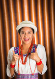 Bautiful hispanic model wearing andean traditional clothing with matching white hat, smiling and interacting using hands Stock Photos