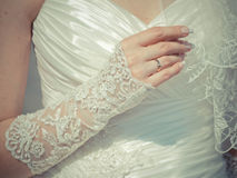 Bautiful ring on the hand of the bride. In white dress stock photo