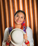 Bautifully dressed hispanic model wearing andean traditional clothing, holding up matching white hat, facing camera. Smiling, beige studio curtain background Stock Image