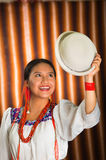 Bautifully dressed hispanic model wearing andean traditional clothing, holding up matching white hat, facing camera. Smiling, beige studio curtain background Royalty Free Stock Photo