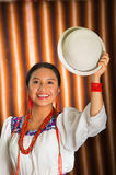 Bautifully dressed hispanic model wearing andean traditional clothing, holding up matching white hat, facing camera. Smiling, beige studio curtain background Royalty Free Stock Photos