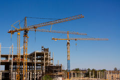 BauTurmkrane und hohes Gebäude im Bau gegen blauen Himmel Lizenzfreies Stockbild