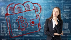 Bauty business woman standing in suit with Bitcoin Logo to illustrate the use of bitcoin for trading or money transfer. Royalty Free Stock Images