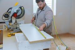 Bauunternehmerarbeitskraft, die das Messen und die Markierung eines Brettes vor dem Schnitt des hölzernen Regals verwendet stockbilder