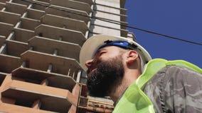 Bauvorarbeiter mit einem Bart und einem Schnurrbart, die im Bau einen Sturzhelm vor dem hintergrund eines Hauses tragen 4K stock video footage