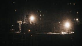 Bauwohngebäude, Arbeitskräfte konstruieren am Schneien Winternachtder ungünstigen Wetterbedingungen stock video footage