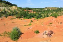 Bauxite. Old out of use open-pit bauxite mine in Gant Hungary with green vegetation Stock Photos