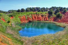 Bauxite quarry. In this photo is represented the quarry of Bauxite, located near Otranto, a city in the south of Italy. Red earth, surrounded by green trees Royalty Free Stock Photos