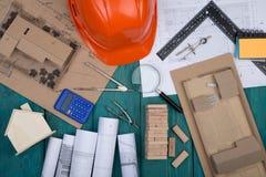 Bauzeichnungen und Technikwerkzeuge, wenig Haus, Musterhaus von den Holzklötzen, Lupe, Taschenrechner, Sturzhelm stockbilder