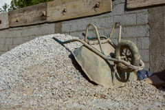 Bauzement, der mit alter Schubkarre und Sand und Grab macht; Stockfoto