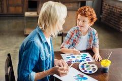 Bavardage d'enfant observé par bleu adorable avec la grand-maman Images stock