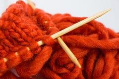 Bavardez et des aiguilles de tricotage d'isolement sur le fond blanc Photos stock
