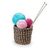 Bavardez et des aiguilles de tricotage disposées dans un panier Photographie stock