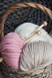 Bavardez les boules avec des aiguilles de tricotage dans le panier sur le fond en bois Photographie stock