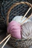 Bavardez les boules avec des aiguilles de tricotage dans le panier sur le fond en bois Image stock