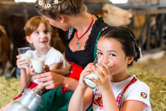Bavaria family drinking milk in cow barn Stock Image