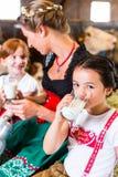 Bavaria family drinking milk in cow barn Royalty Free Stock Photo