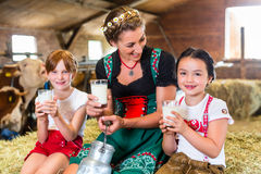 Bavaria family drinking milk in cow barn Royalty Free Stock Image