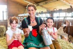 Bavaria family drinking milk in cow barn Royalty Free Stock Photos