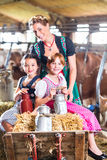 Bavaria family driving pushcard in cow barn. Bavarian mother driving children on pushcard with hay bale through cowhouse Royalty Free Stock Images