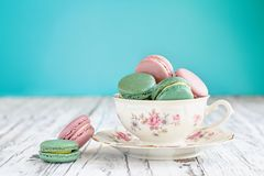 Bavaria Winterling Footed Tea Cup Filled with Macarons. Antique Bavaria Winterling footed tea cup from the 1950s` filled with pink strawberry and green tea stock images