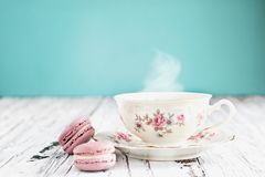 Bavaria Winterling Footed Tea Cup with Macarons. Antique Bavaria Winterling footed tea cup from the 1950s` with pink macarons on a rustic white table against a royalty free stock photo