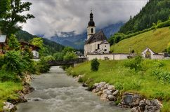 In the Bavarian Alps. The alpine village of Ramsau with an ancient church and a wild river Stock Photography