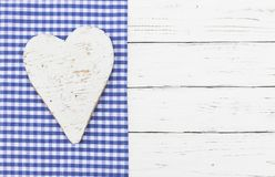 Bavarian background with white wooden heart on blue checked fabric border and white wood. Rustic white heart on bavarian blue checked textile and white wooden royalty free stock photo