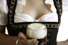 Bavarian beer girl holds Oktoberfest beer stein. In front of breast Royalty Free Stock Photos