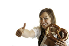 Bavarian beer girl at Oktoberfest with pretzel. Express happiness with thumb up Stock Photography