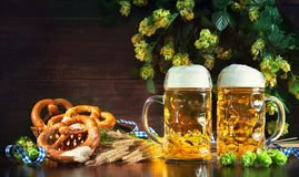 Bavarian beer with soft pretzels, wheat and hop on rustic wooden Stock Photos