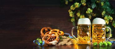 Bavarian beer with soft pretzels, wheat and hop on rustic wooden Royalty Free Stock Photo