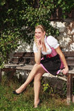 Bavarian blond girl sitting relaxed on a bench in a dirndl. Royalty Free Stock Photography