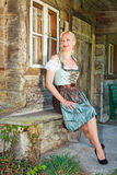 Bavarian blonde woman sitting elegantly in a dirndl. Bavarian blonde woman in dirndl sitting elegantly on a bench in front of an old farmhouse, Exterior royalty free stock image