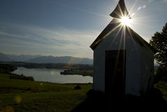 Bavarian chapel silhouette. A silhouetted view of a small chapel overlooking a lake in Bavaria with the sun just peeking around a corner of the chapel steeple Royalty Free Stock Photos