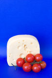 Bavarian Cheese With Cherry Tomatoes. Food & Drinks - Cheese. Piece of soft creamy bavarian cheese with cherry tomatoes isolated on blue background Stock Images