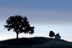 Bavarian countryside at dusk. Small church and trees silhouetted against evening sky Royalty Free Stock Image