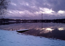 Bavarian countryside,winter landscape  -  lake of Eching by nigh. Night view of Bavarian  lake on winter with small pier, snow and clouds reflecting on the calm Royalty Free Stock Photo
