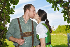 Bavarian couple kissing each other. Couple in traditional bavarian clothes standing underneath bushes and kissing each other Royalty Free Stock Photo