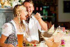 Bavarian Couple in restaurant eating Royalty Free Stock Image