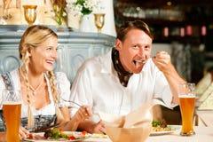 Bavarian Couple in restaurant eating Stock Photos