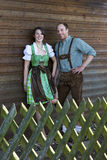 Bavarian couple standing behind a wooden fence Royalty Free Stock Photo