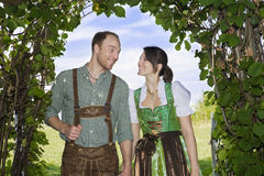 Bavarian couple standing underneath a tree. Couple in traditional bavarian clothes standing underneath a tree stock images