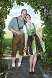 Bavarian couple standing underneath a tree Stock Images