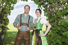 Bavarian couple standing underneath a tree. Couple in traditional bavarian clothes standing underneath a tree royalty free stock image