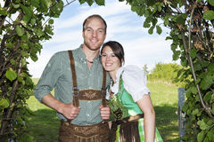 Bavarian couple standing underneath a tree Stock Photo